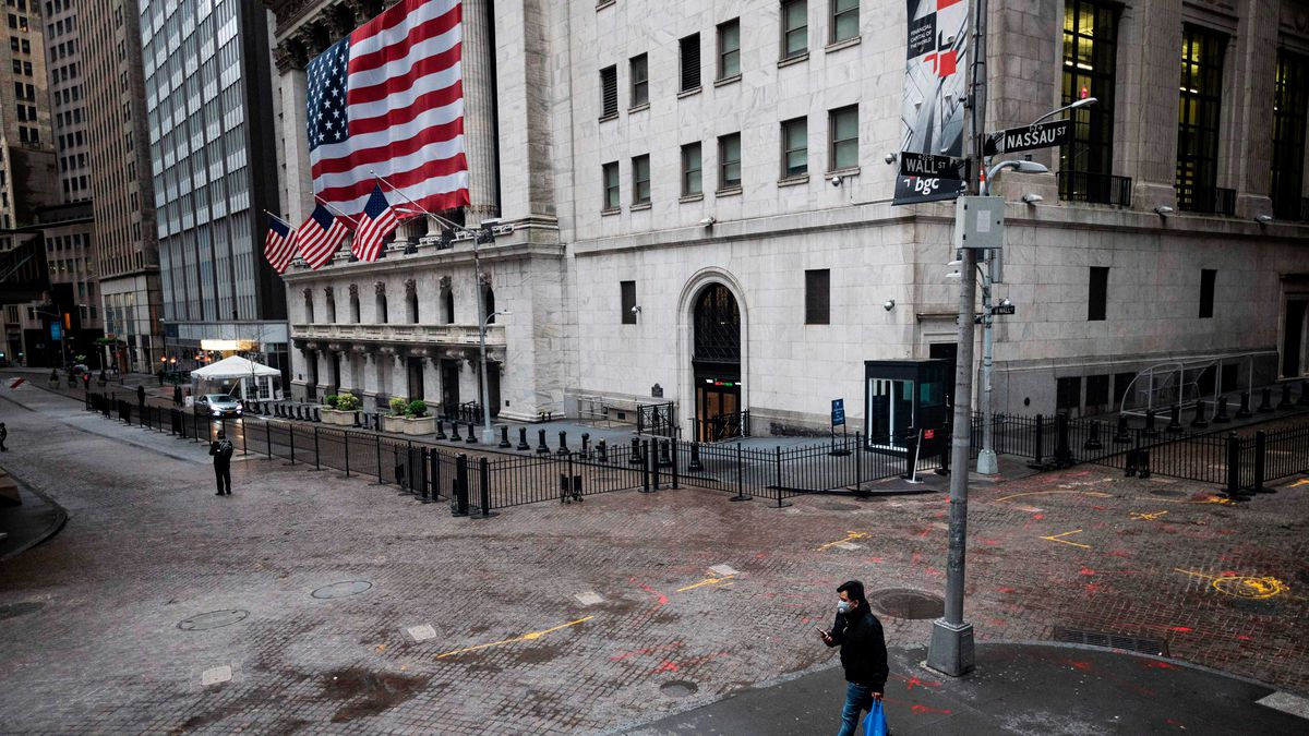 A man in a mask walks by the New York Stock Exchange.