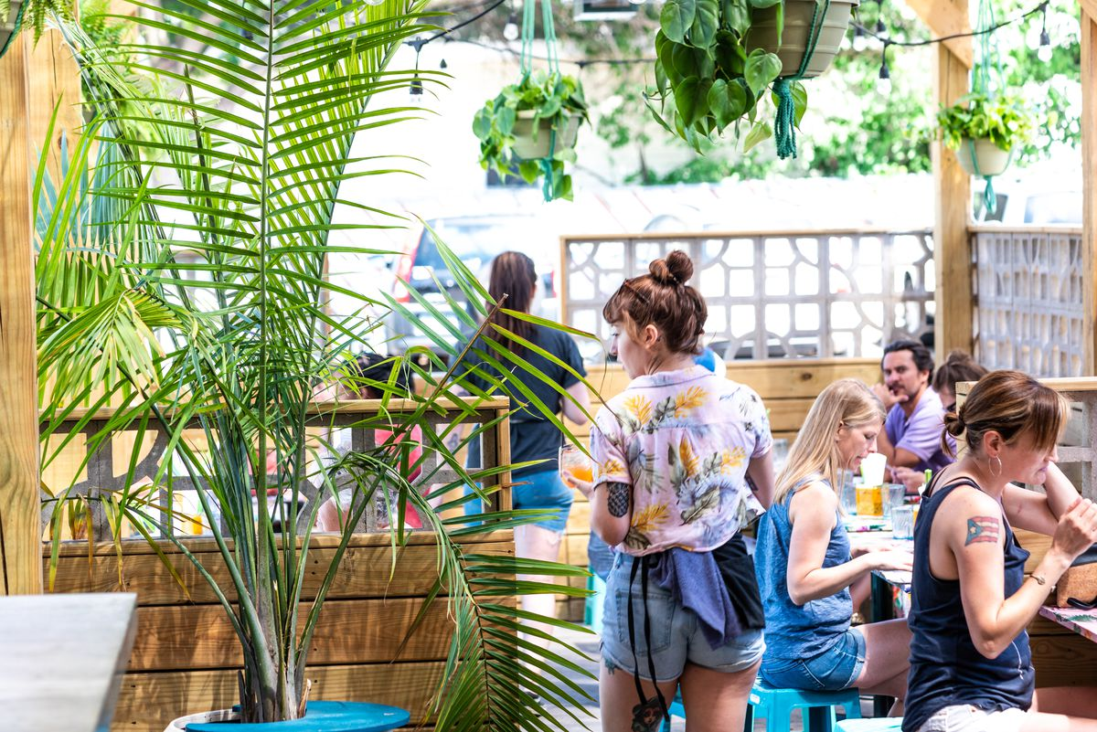 A bustling patio basked in sunlight. A server in a floral shirt carries drinks.