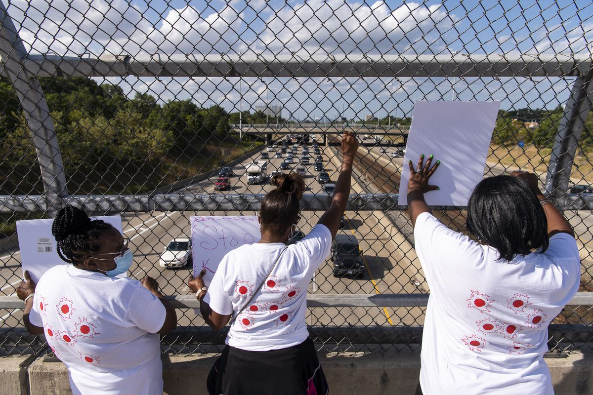 """A group anti-violence activists from Saint Sabina hold up signs that read """"Stop Killing Us"""" on the 76th Street Overpass that crosses over the Dan Ryan Expressway, Friday, Aug. 28, 2020. 