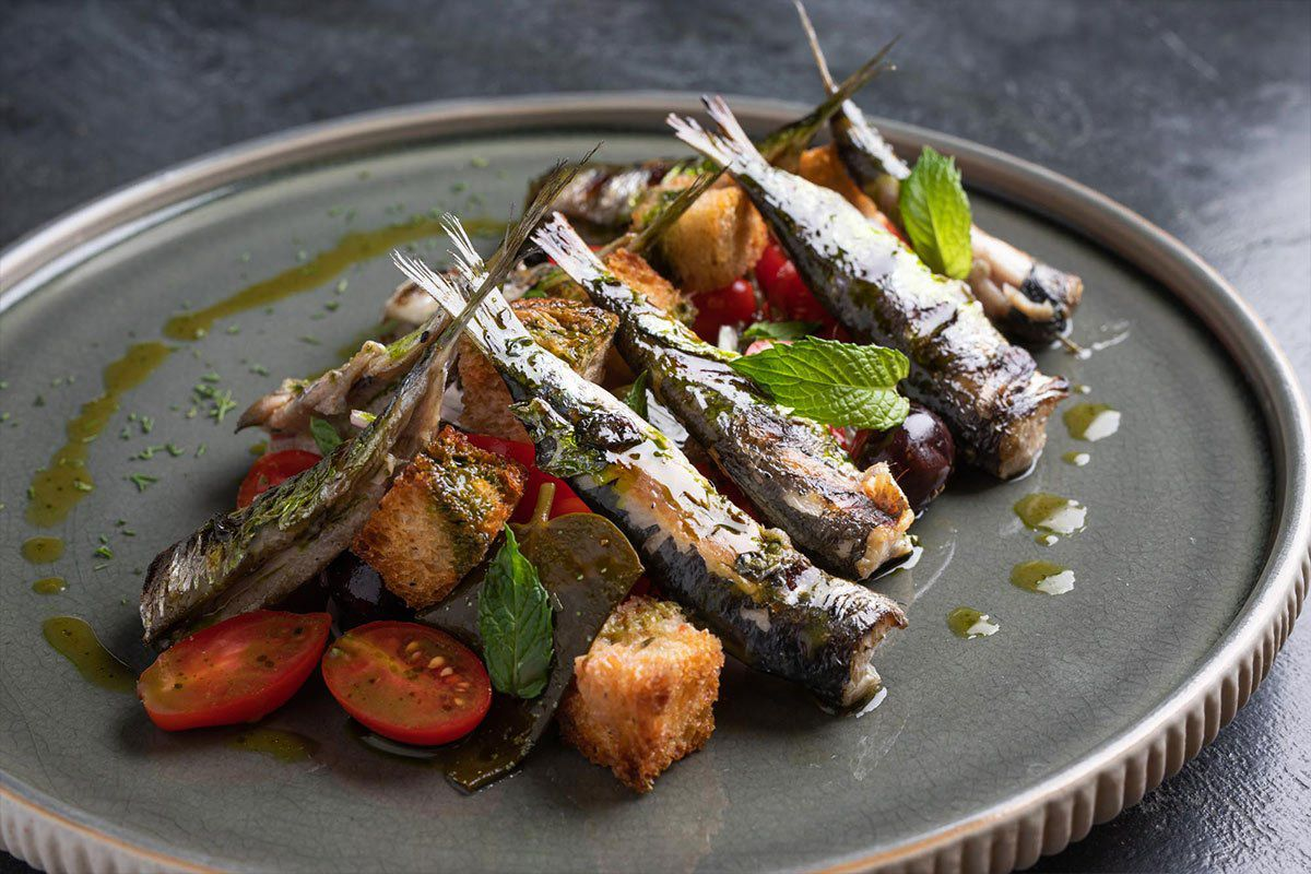 Sardines stacked on a pile of vegetables and crutons