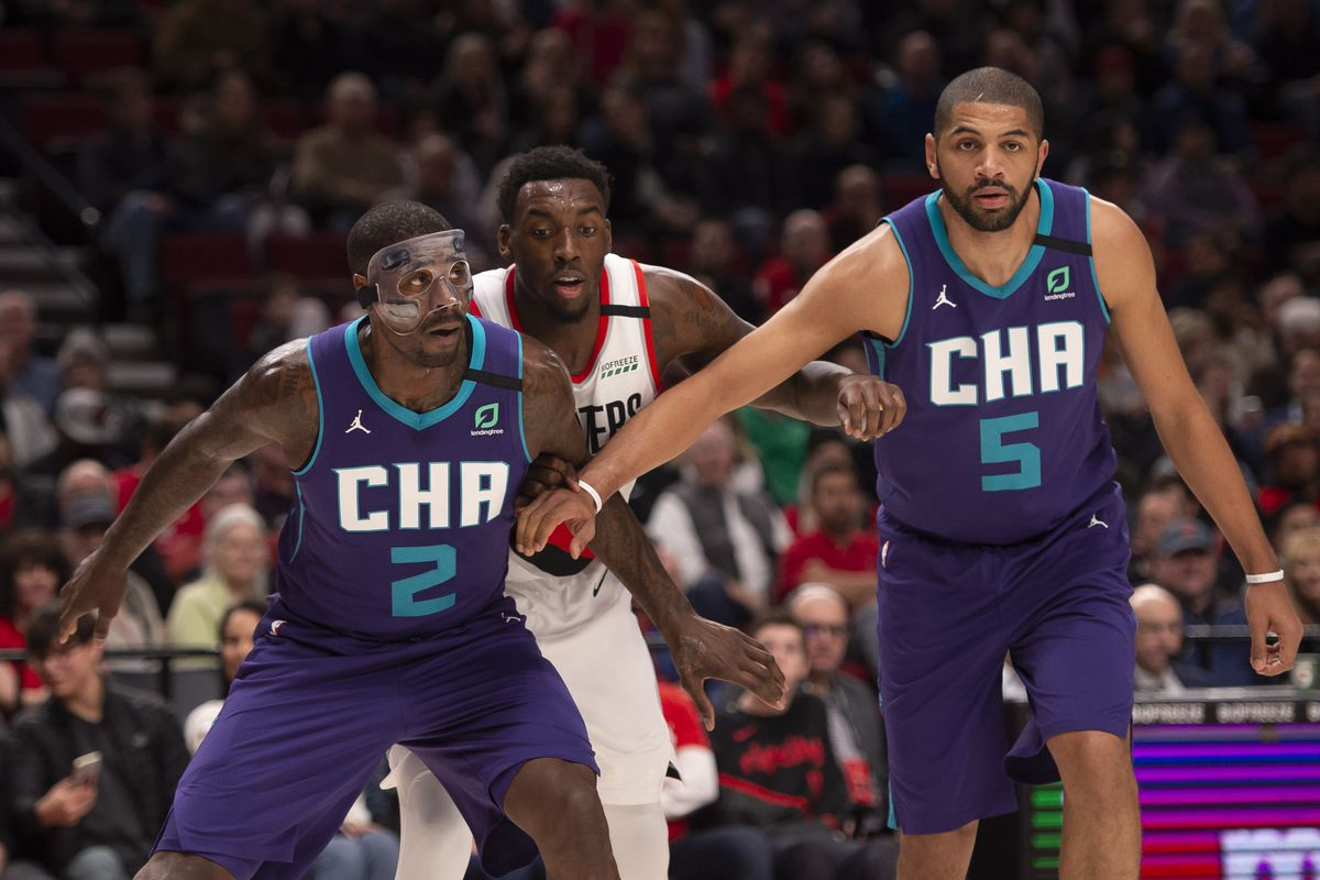 Hornets forward Marvin Williams (2) and guard Nicolas Batum (5) block out Portland Trail Blazers forward Nassir Little (9) during the first half at Moda Center.