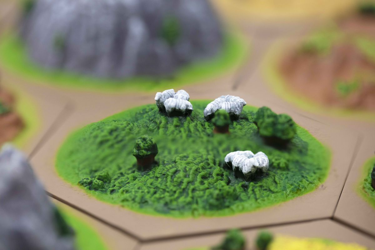 A pasture, complete with a few sheep on a hill.