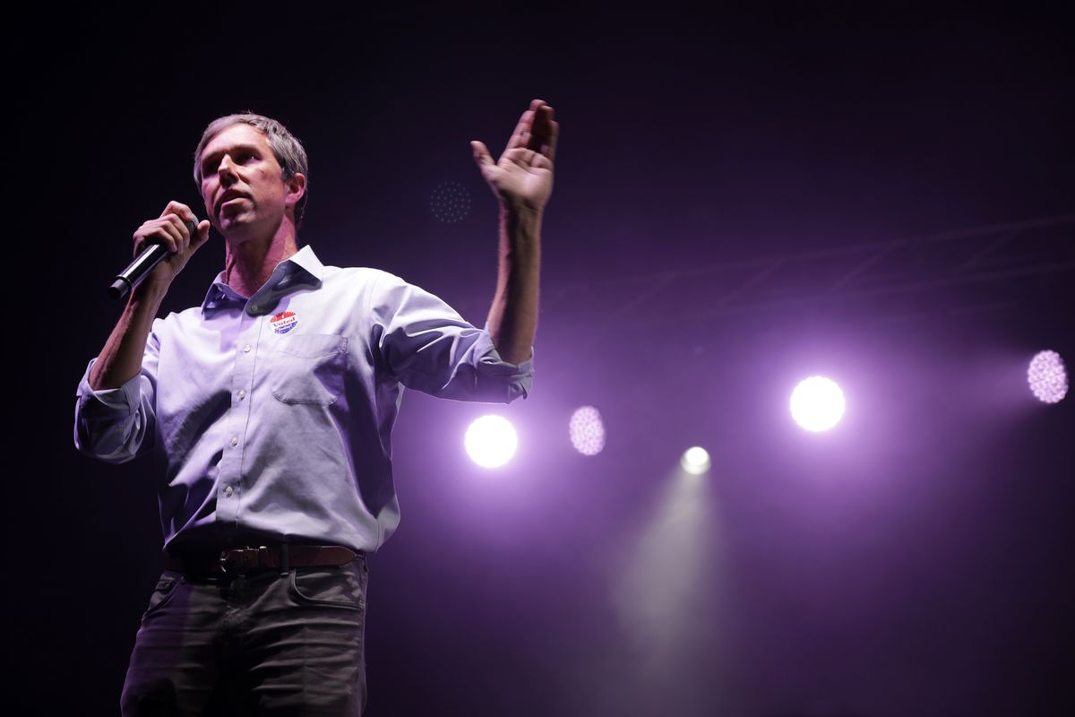 Democratic presidential candidate Beto O'Rourke speaking into a hand-held microphone onstage.
