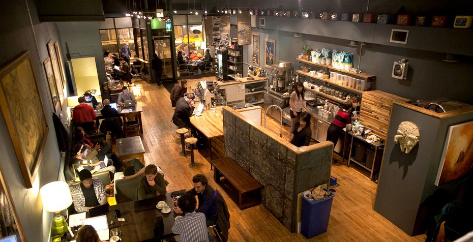 A grey-painted coffee shop from above filled with wooden tables, '80s memorabilia, and customers.