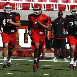 Utah quarterback Terrance Cain, center, runs with teammates during practice Monday at Rice-Eccles Stadium.
