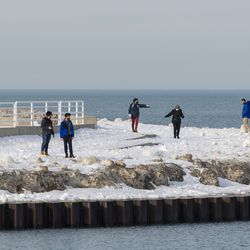 A group of people walk along the lakefront near the mouth of Diversey Harbor, Tuesday, Feb. 23, 2021. The Chicago Parks District reopened the Lakefront Trail Tuesday.