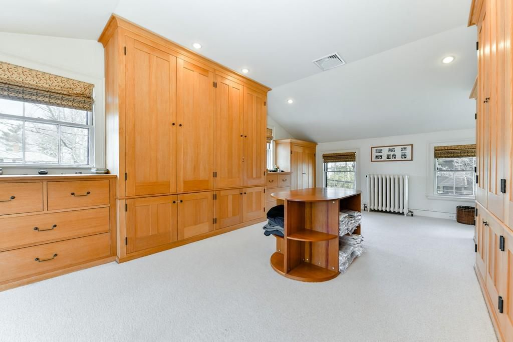 A massive walk-in closet with large cabinets on either side and a set of shelves in the middle.