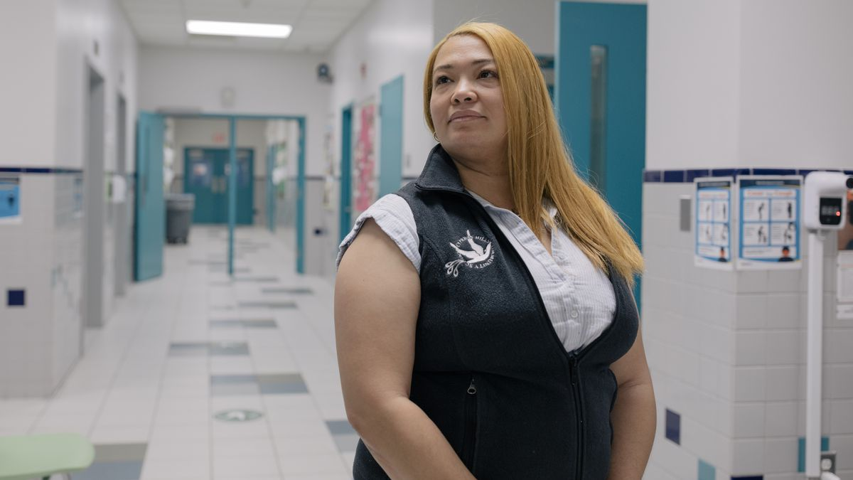 A woman with golden hair wearing a blue vest poses for a portrait in a school hallway.