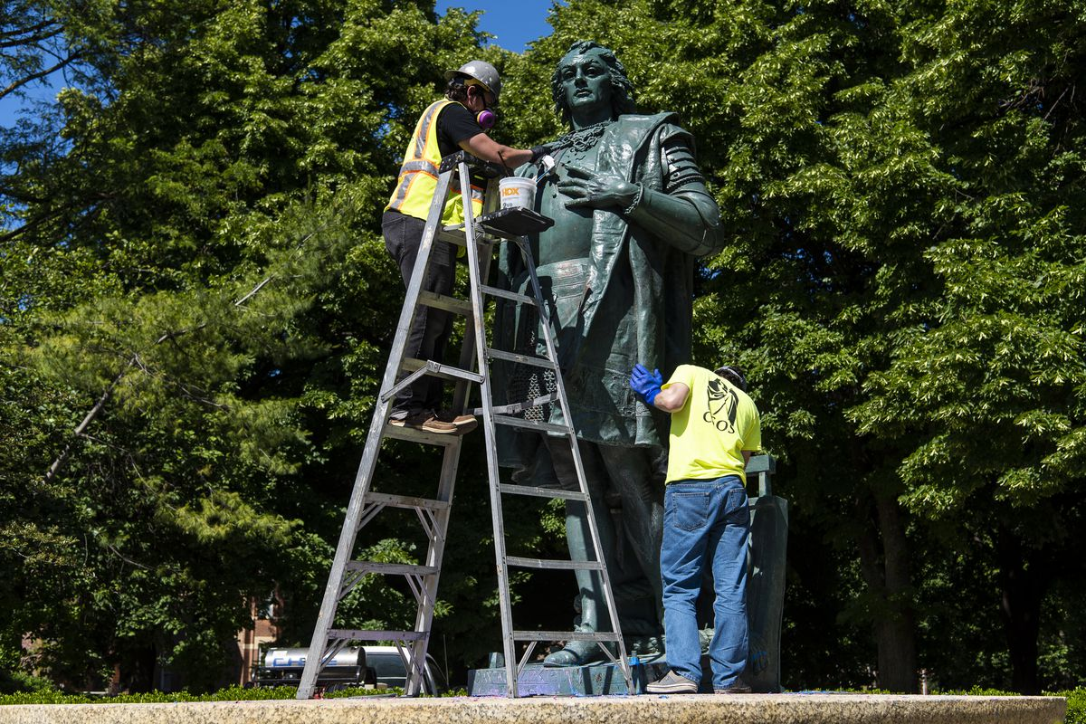Workers with We Save Art clean paint from a Christopher Columbus statue located in Arrigo Park at 801 S. Loomis St. on June 15, 2020.