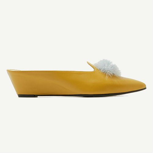 Yellow loafers with white pom poms.