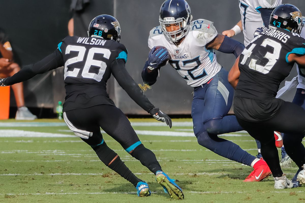 Tennessee Titans running back Derrick Henry (22) runs the ball past Jacksonville Jaguars free safety Jarrod Wilson (26) during the second half at TIAA Bank Field