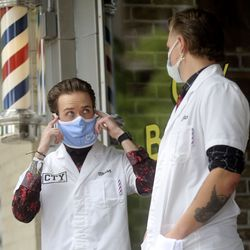 City Barbers manager Ace Parkin, left, talks to barber Nick Hulbert about an upcoming client's haircut outside of City Barbers on Broadway between 200 East and 300 East in Salt Lake City on Thursday, June 18, 2020.
