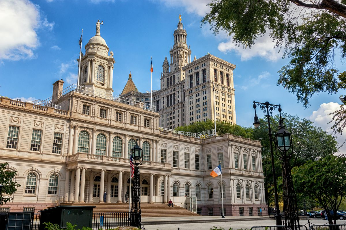 The exterior of New York City Hall. The facade is tan and there are two towers. There is a staircase leading to the entrance.