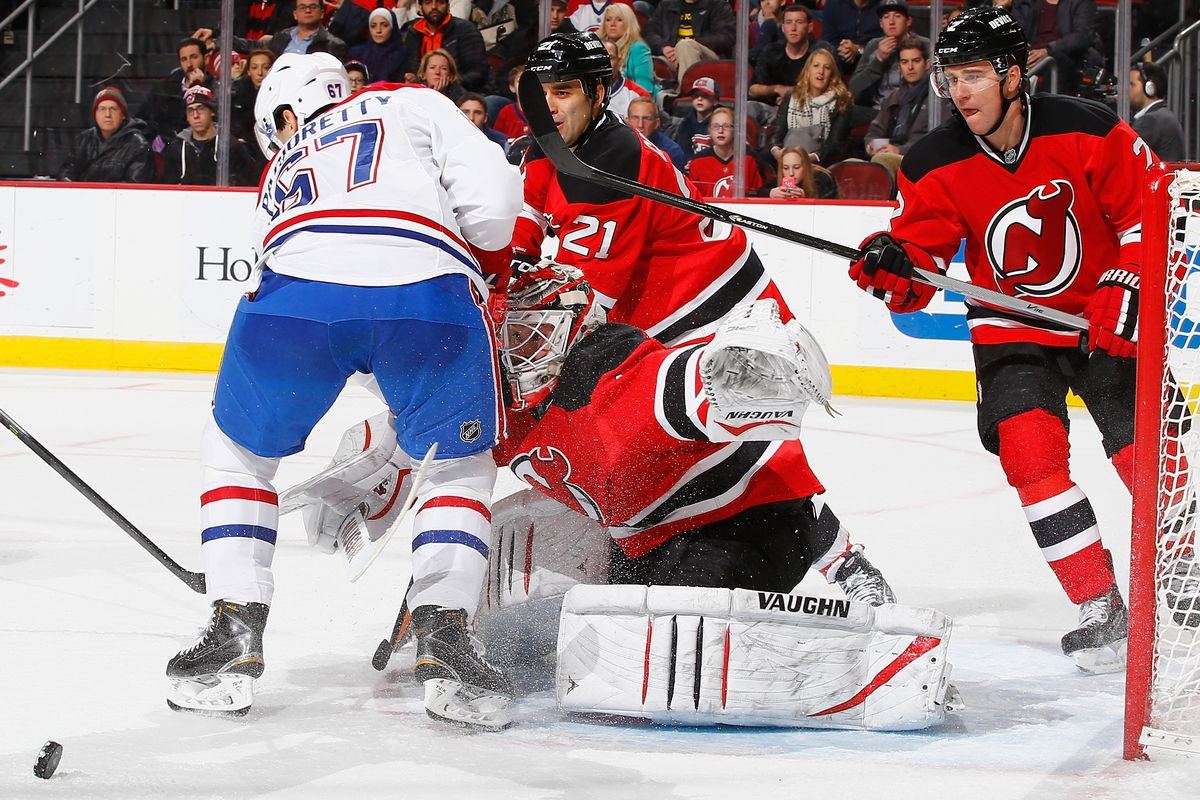 Max Pacioretty #67 of the Montreal Canadiens crashes into Keith Kinkaid #1 of the New Jersey Devils during their game at the Prudential Center on January 2, 2015 in Newark, New Jersey.