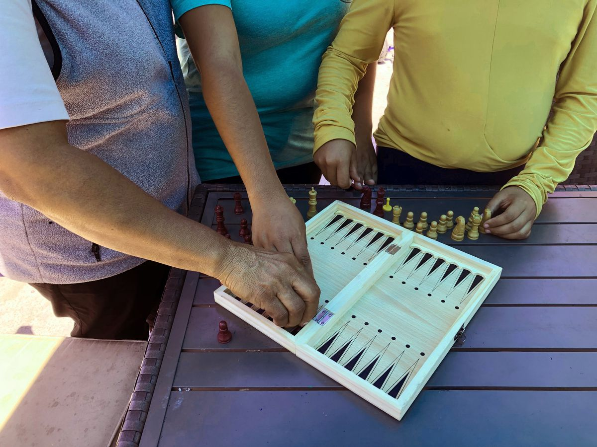 (From left) Luz Viviana Perez, 53, arranges a chess board with her daughters, 17 and 12. at a migrant shelter in San Diego where the family, from Mexico, is seeking asylum.