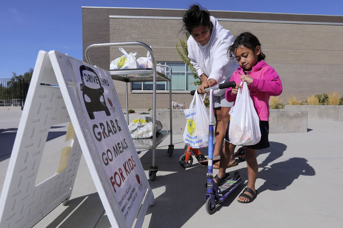 Roxy Penaloza helps Teke Vea load up bagged lunches on her scooter outside of Edison Elementary School in Salt Lake City on Monday, Sept. 28, 2020. Nutrition technicians and kitchen managers typically hand out between 300 to 400 lunches a day at Edison. Meal service hours have extended and will now go from 10:30 a.m. to 12:30 p.m.