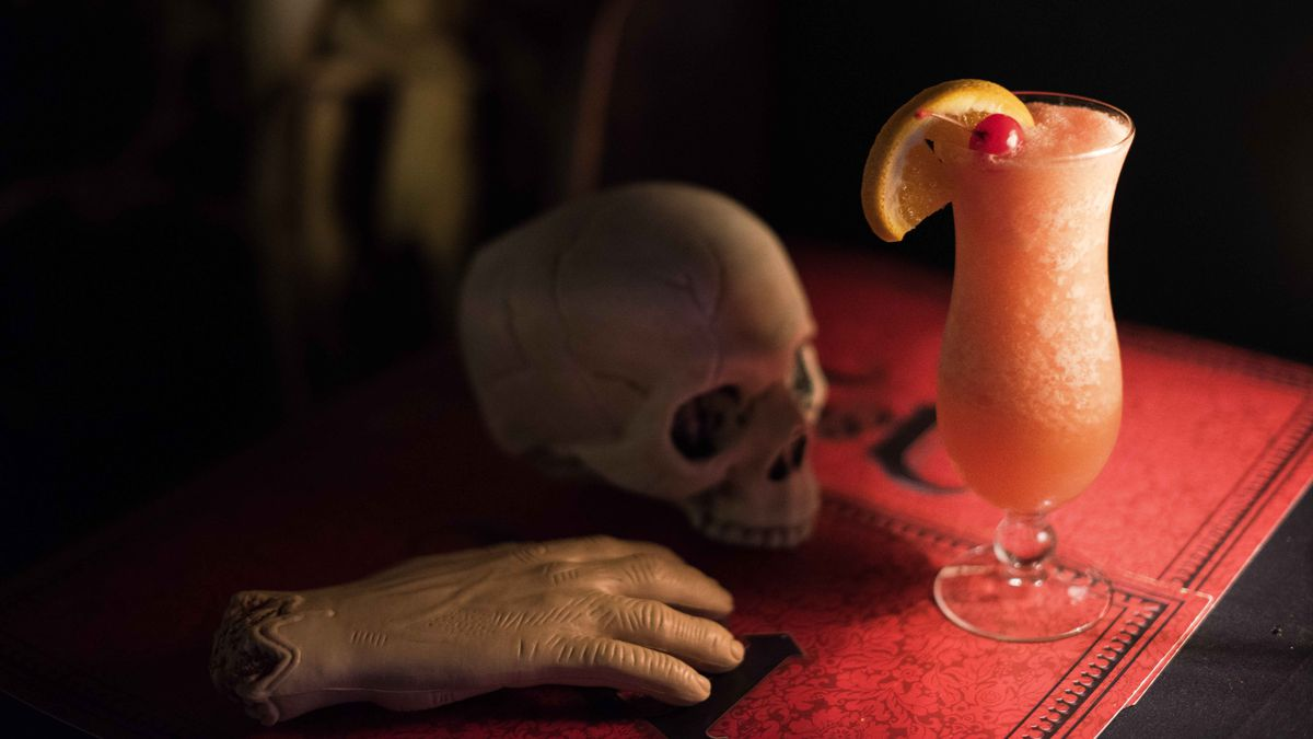 """A toy severed hand, plastic skull, and the """"Transformation Cocktail"""" in a glass with a cherry and lemon wedge garnish."""