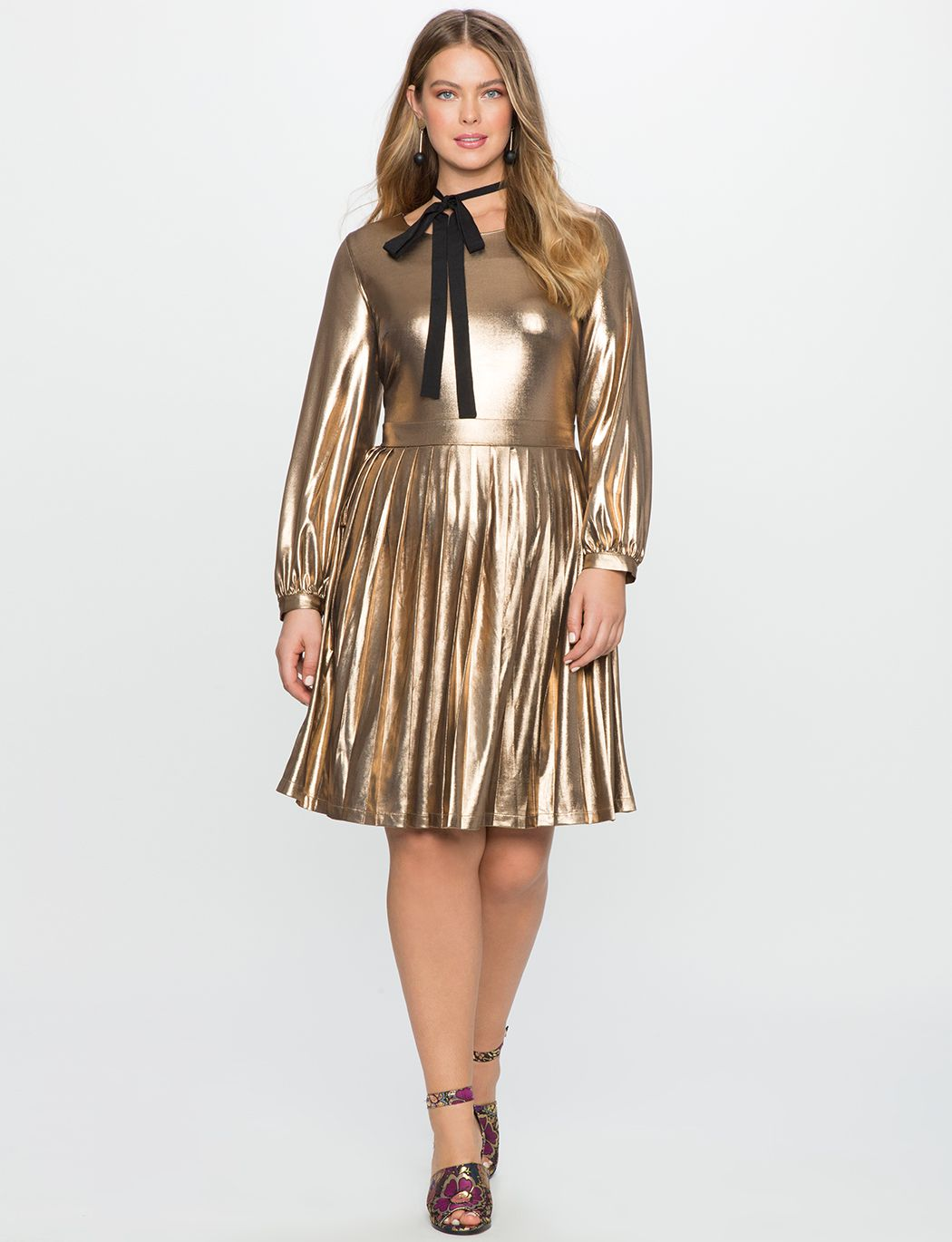 A model in a gold metallic fit and flare dress
