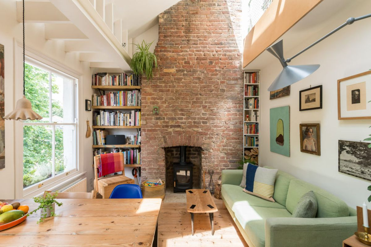 Interior shot of living space looking onto exposed brick fireplace with bookshelves built into either side of it. Mint green sofa and large windows brighten the room.
