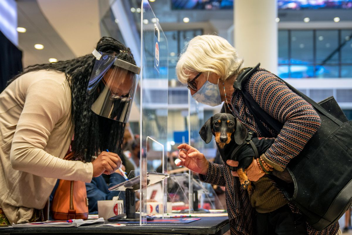 A Manhattan woman and her dog get instruction at Madison Square Garden on the first day of early voting, Oct. 24, 2020.