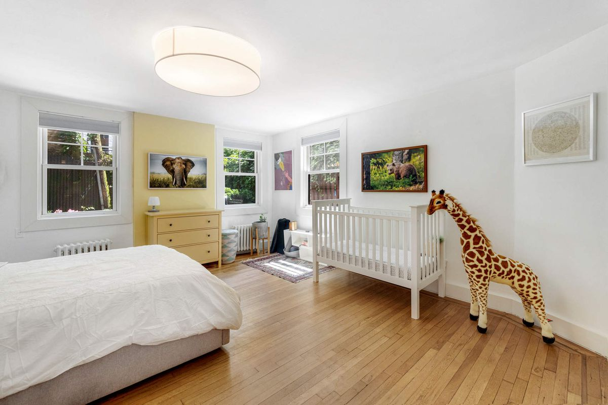 A bedroom with a crib, a toy giraffe, hardwood floors, a bed, and three windows.