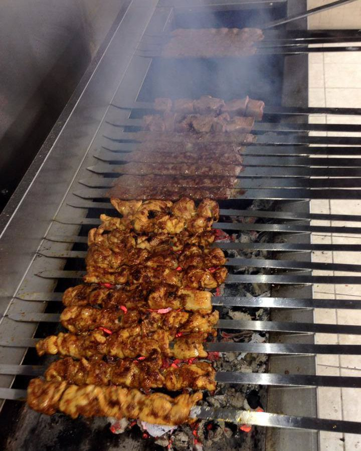 A line up of kebabs on a charcoal grill.