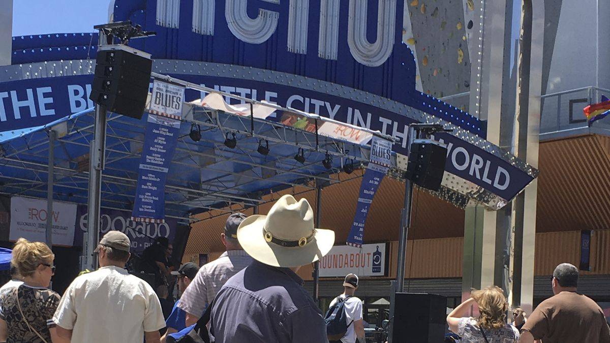 """People, including a man in a cowboy hat, stand in front of a stage with a large sign reading """"Reno."""""""