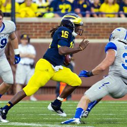 Air Force defensive lineman Nick DeJulio (89) watches as Michigan quarterback Denard Robinson (16) rush past Air Force defensive back Brian Lindsay (31) for a 79-yard touchdown in the first quarter of an NCAA college football game, Saturday, Sept. 8, 2012, in Ann Arbor, Mich.