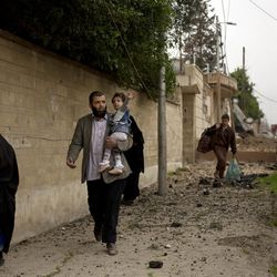 A toddler reaches for an overhead wire as she flees with her family during heavy fighting in the Yarmouk district of western Mosul, Iraq, Tuesday, April 11, 2017.