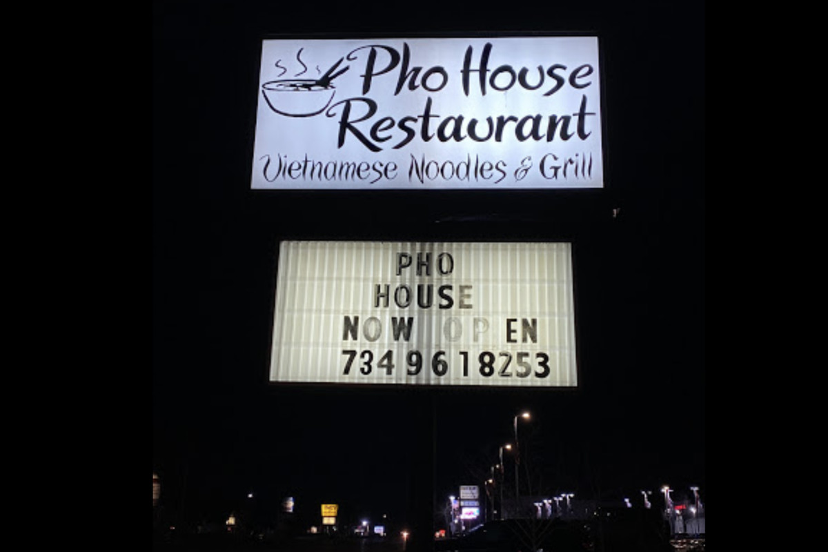 """The Pho House restaurant marquee on a road at night reads """"Now Open"""" with a telephone number listed."""