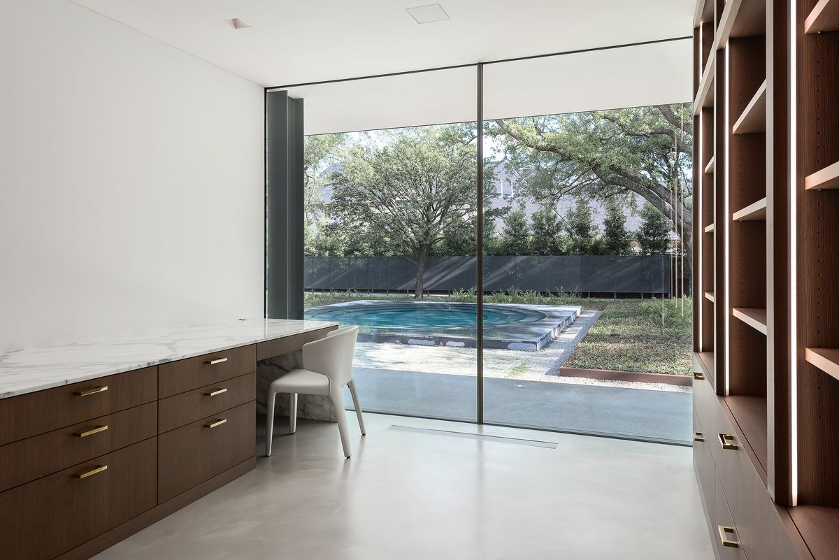 An office with desk, concrete floors, built-in bookshelves, a chair, and glass windows that look out onto a pool.