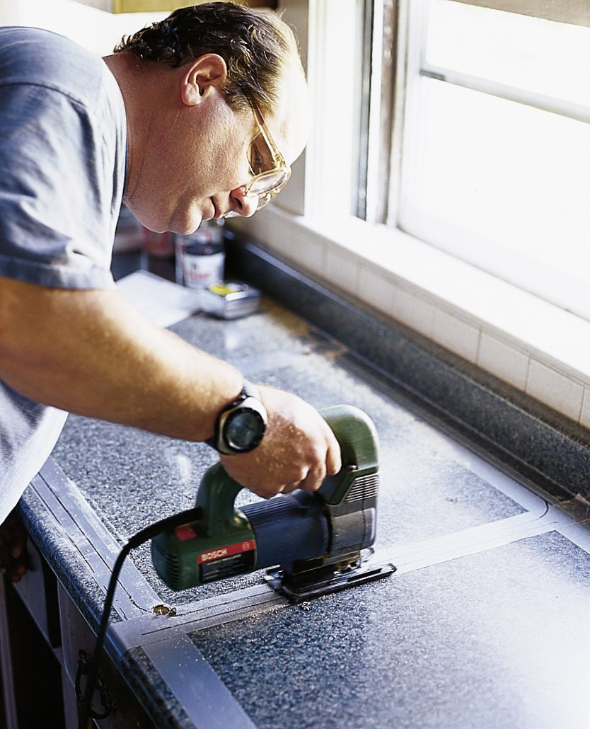 Person using a jigsaw to cut a hole into a kitchen counter.