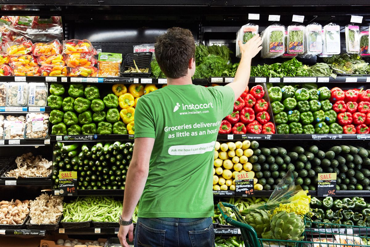 An Instacart shopper chooses items for a grocery order.