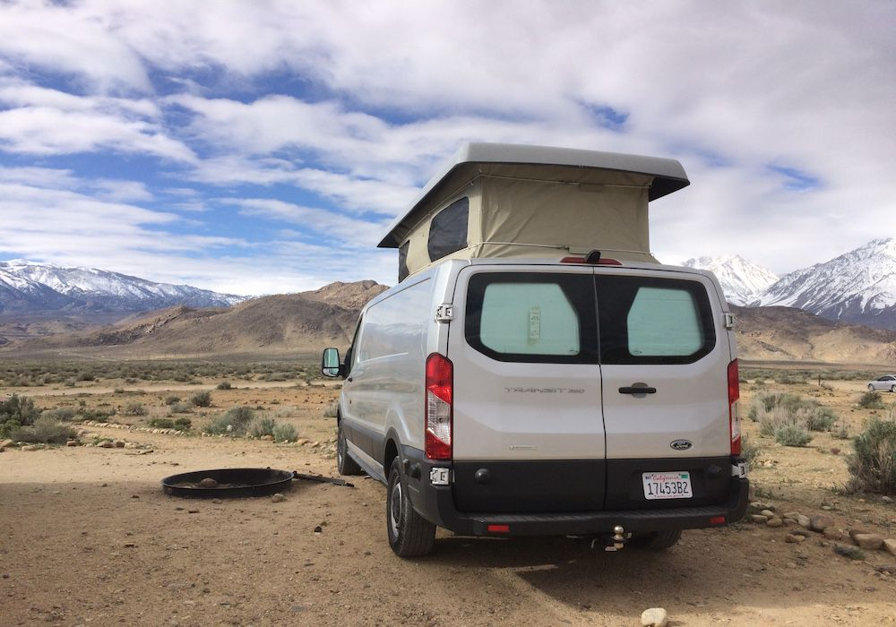 The exterior of a RV camper van.  The van is white and has a compartment above the roof. It is sitting in a desert. There are mountains in the distance.