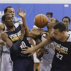 Houston Rockets' B.J. Young (15) battles for a loose ball with Utah Jazz's Rudy Gobert (27), of France, and Jeremy Evans (40) during an NBA summer league basketball game, Tuesday, July 9, 2013, in Orlando, Fla. (AP Photo/John Raoux)