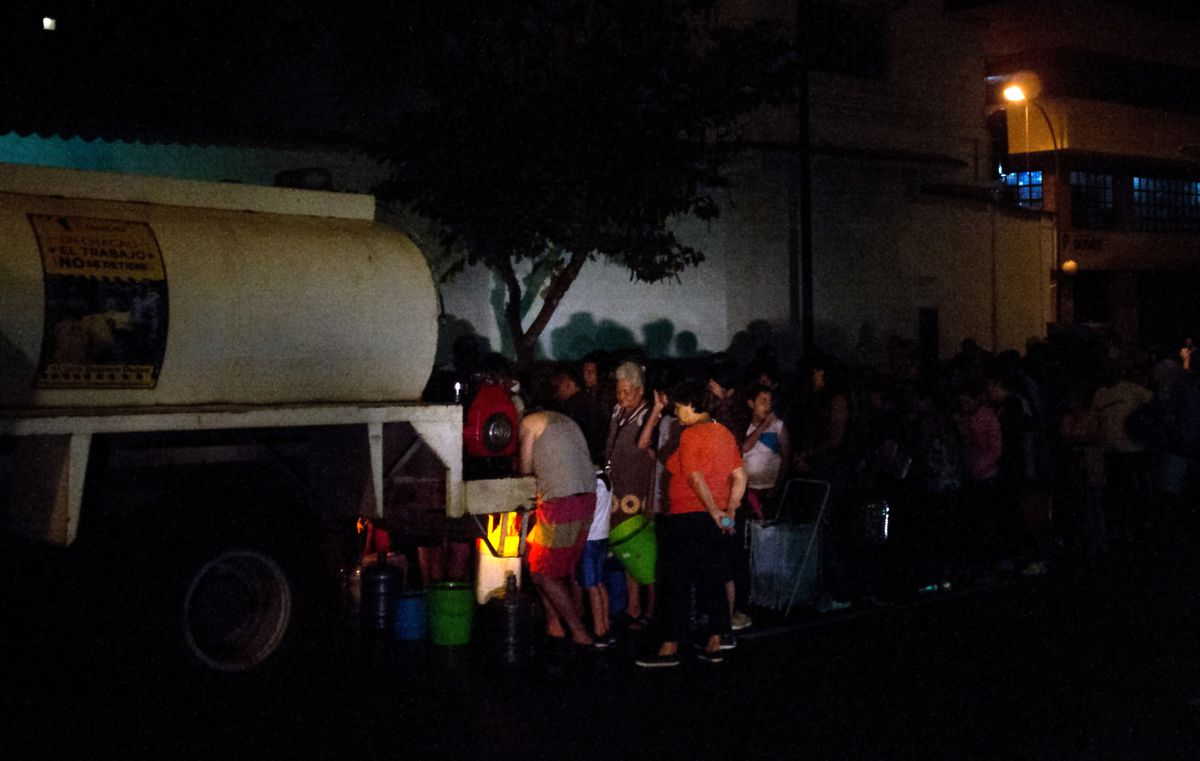 wait in line for drinking water being distributed in a tanker in the municipality of Chacao, in Caracas, on March 11, 2019.
