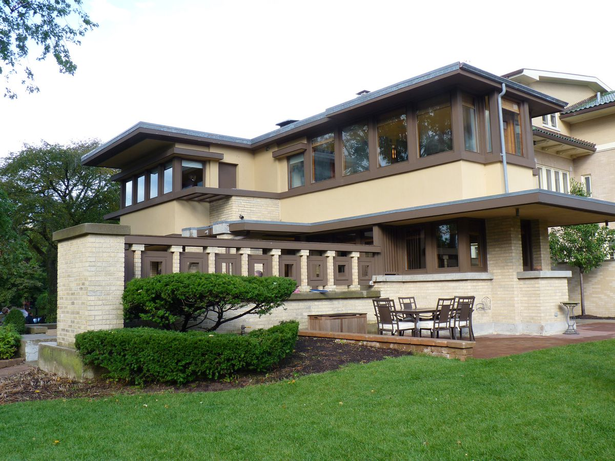 The Emil Bach House by Frank Lloyd Wright. The house is multiple levels and has an ivory facade with dark brown framing. There is a lawn in front with shrubbery.