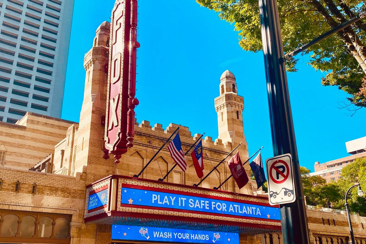 """The outside of the historic Fox Theatre on Peachtree Street in Atlanta with the marquee displaying """"Play it safe for Atlanta"""" and """"Wash your Hands"""" on a sunny day with bright blue skies during the pandemic 2020"""