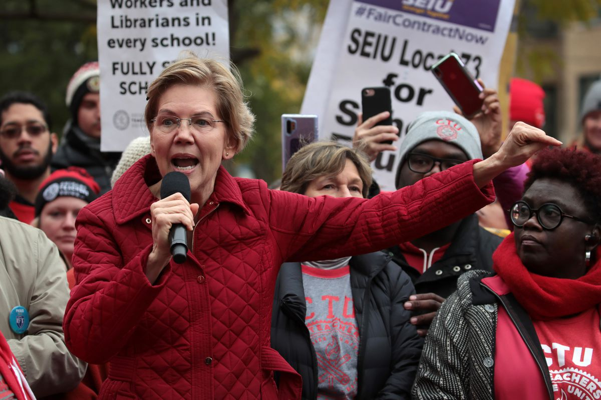 Democratic presidential candidate Senator Elizabeth Warren speaking into a handheld microphone and surrounded by picketing Chicago teachers and their supporters.