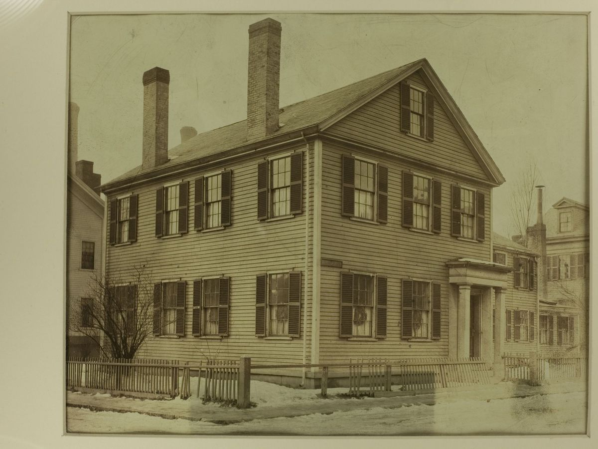 Black-and-white photograph of a two-and-a-half-story house with two chimneys.