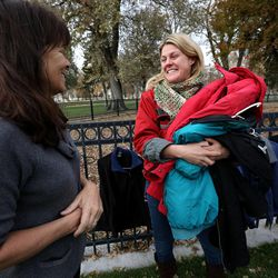 Laurie Summers-Pisani and Karon Barnes chat at the 10th annual Community Coat Exchange at Pioneer Park in Salt Lake City on Friday, Nov. 28, 2014.