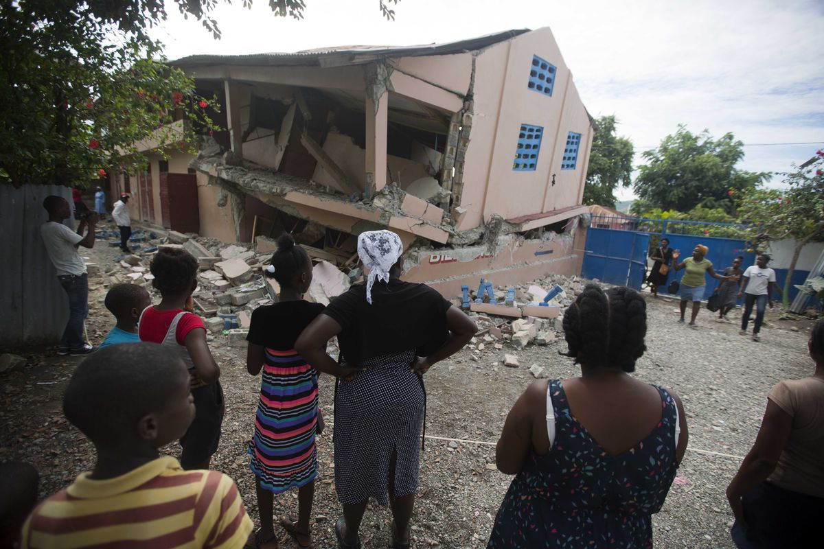Residents stand looking at a collapsed school damaged bya magnitude 5.9 earthquake the night before, in Gros Morne, Haiti, Sunday, Oct. 7, 2018. Emergency teams worked to provide relief in Haiti on Sunday after the quake killed at least 11 people and left