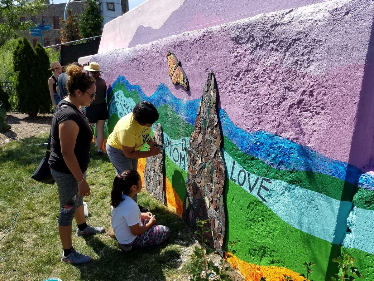 Students and parents work on a mural and mosaic project in 2017 near McAuliffe Elementary School in Logan Square that the school's students created.