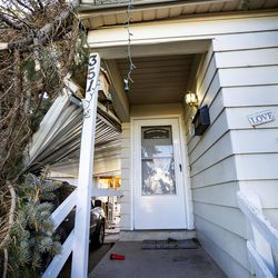One of two large pine tree felled by high winds rests on Lyle Bair's home inWashington Terrace on Tuesday, Jan. 19, 2021. One of the felled tree damaged Bair's carport, his car and other items.