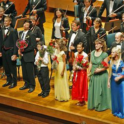 Conductor David Cho presents winners Christian Hales, Ubeeng Kueq, Trenton Chang, Aubree Oliverson, Verina Chen, Gabriella  Roderer, Camille Johnson and Sara Noel Bauman at the 50th anniversary Salute to Youth concert Tuesday in Salt Lake City.