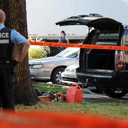 A police officer looks towards a black vehicle that has had its contents removed at a crime scene outside the Metropolis in Montreal on Wednesday, Sept. 5, 2012.  A masked gunman wearing a blue bathrobe opened fire during a midnight victory rally for Quebec's new premier, killing one person and wounding another. The new premier, Pauline Marois of the separatist Parti Quebecois, was whisked off the stage by guards while giving her speech and uninjured. It was not clear if the gunman was trying to shoot Marois, whose party favors separation for the French-speaking province from Canada. Police identified the gunman only as a 62-year-old man, and were still questioning him Wednesday morning.