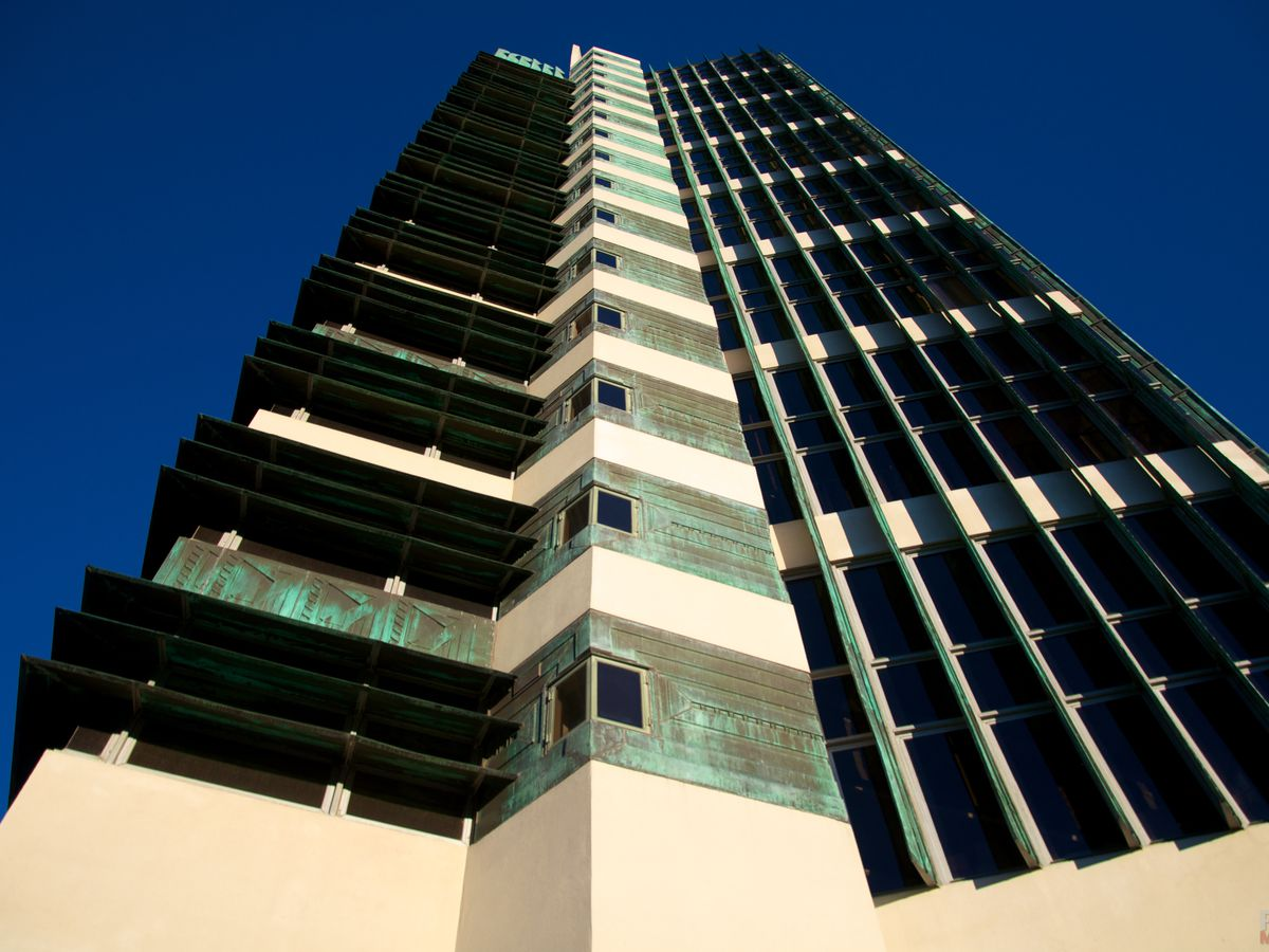 The Price Company Tower by Frank Lloyd Wright. The facade is tan and copper with angled walls and an asymmetrical design.