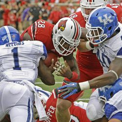 Louisville running back Jeremy Wright (28) muscles through Kentucky defenders Martavius Neloms (1) and Avery Williamson (40) to score the first touchdown of the year during an NCAA college football game at Cardinal Stadium in Louisville, Ky., Sunday, Sept. 2, 2012.