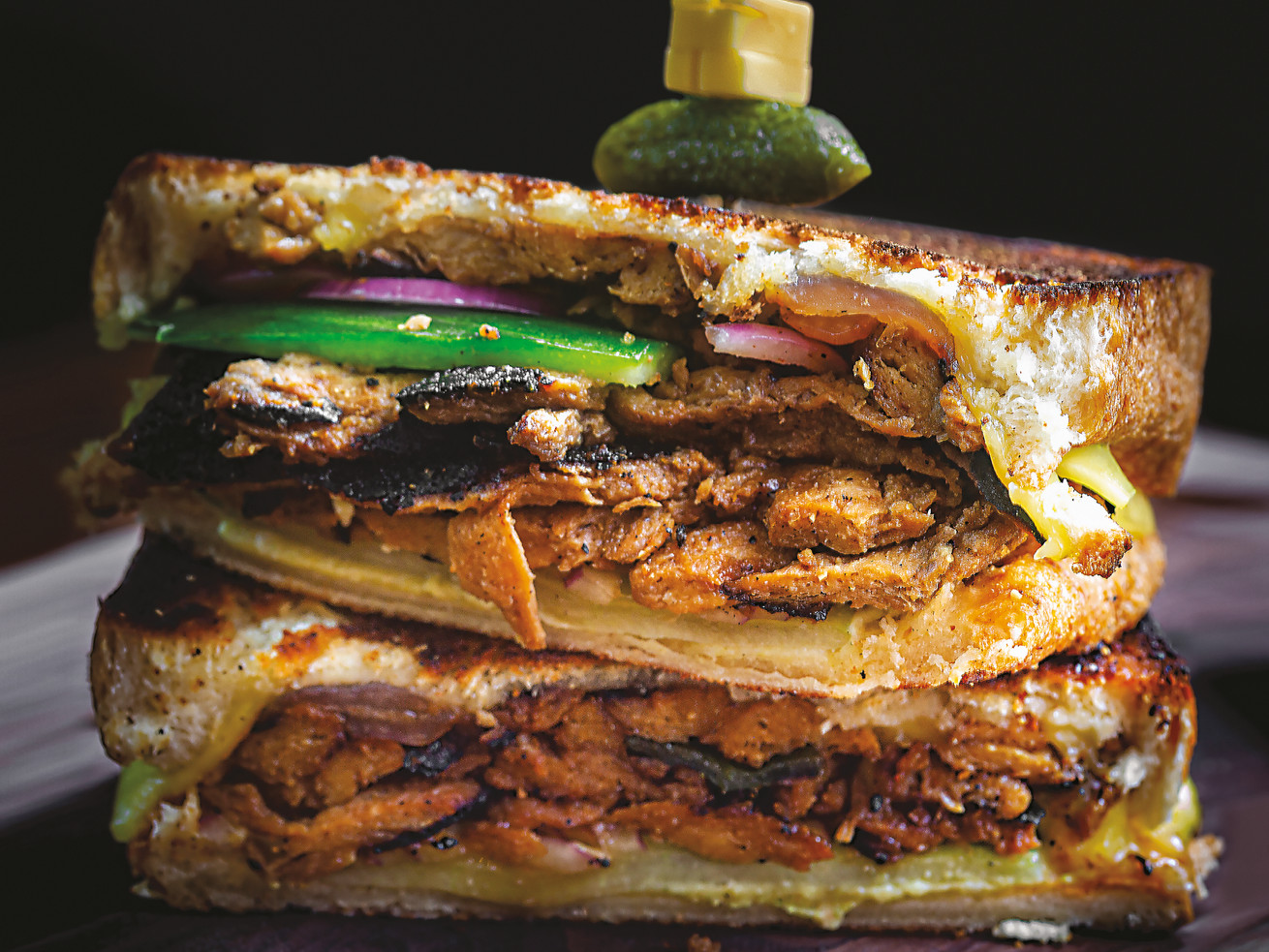 A toasted sandwich sliced in half so you can see the interior, filled with green pepper, onion, and bulgogi