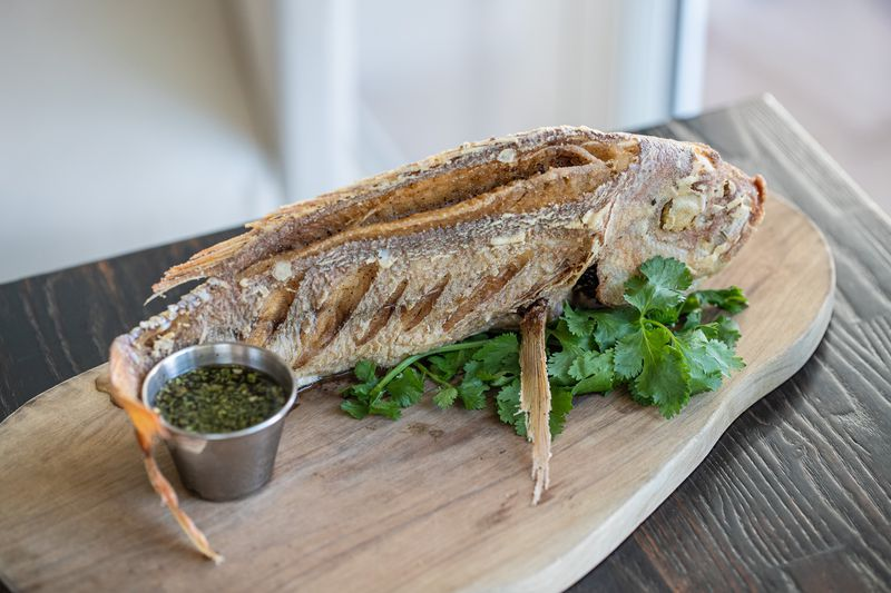 Whole fried fish on a wooden plank with herb fish sauce.